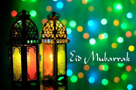 Eid Mubarak greeting with arabic lamp and colorful blur background