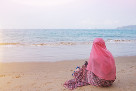 religious clothing: muslim girl look out the sea