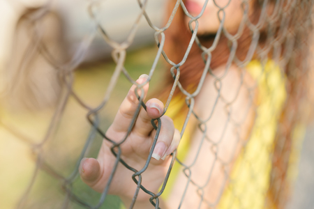Young woman hand holding metal net fence.