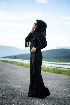 Fashion portrait of young beautiful muslim woman with the black hijab and full black dress.Vintage style Stock Photo