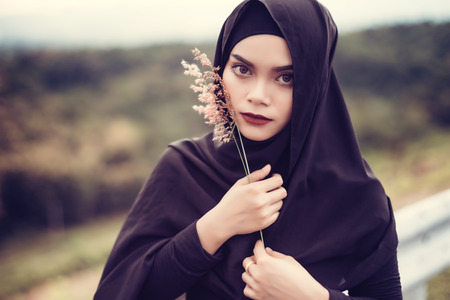 Fashion portrait of young beautiful muslim woman with the black hijab.Muslim woman holding grass flower.Vintage style Stock Photo