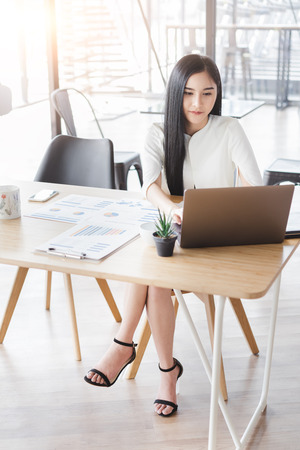 Asian beautiful young business woman in white shirt smiling working on desk with laptop and financial report document.