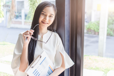 Asian beautiful young business woman in white shirt hand holding spectacles eyeglasses and financial report document.