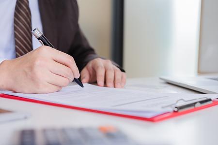 Hände des Geschäftsmann braunen Anzugs unterzeichnen Vertragsvereinbarung. Konzept der Vertragsvereinbarung.