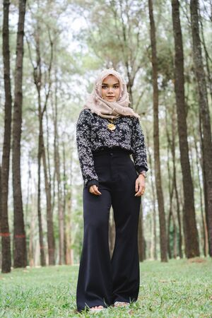 Portrait of happy young muslim woman mellow yellow hijab over blurred the pine forest background. Vintage tone. Imagens