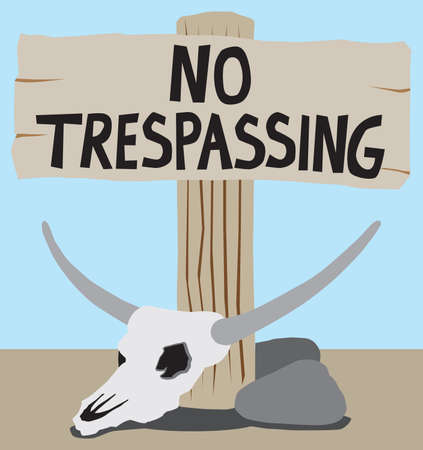 A steer skull is resting against a no trespassing sign in the desert