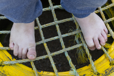A Small boys feet standing on top of a yellow tire with netting sowen into the middle