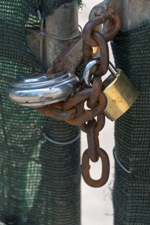 A close up front view of two locks and a old rusted chain securing a matal gate with green mesh on
