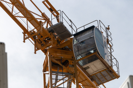 A close up view from the ground of the drivers cab of a yellow crane working on a construction site