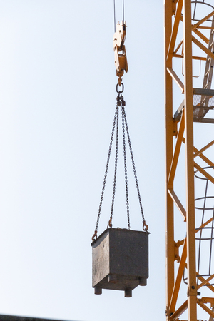 A Close up view of the arm of a yellow crane liftting up a metal box on a construction site 스톡 콘텐츠