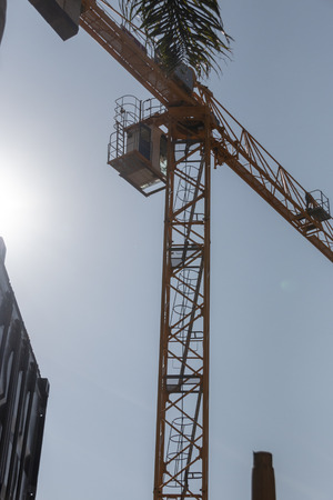 A close up view from the ground of a yellow crane working on a construction site with a the conner of a grey container on the side