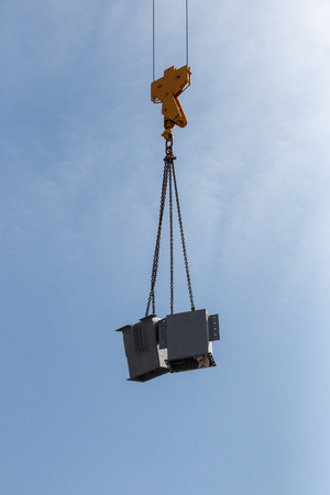 A Close up view of the arm of a yellow crane liftting up a metal stands on a construction site
