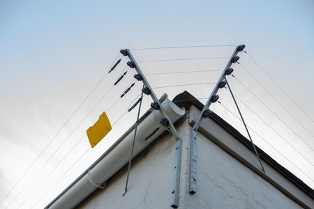 A Close up view of electric fencing around the top side of a white building Stockfoto