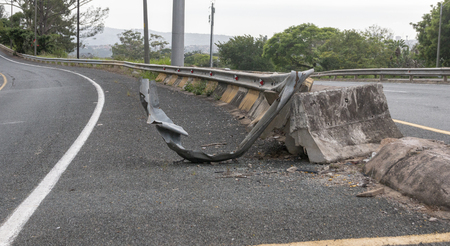 A close up view of the metal and concrete bolck barrier on the side of a freeway or motorway that has been damaged by a car or motor vehicle crashing into it