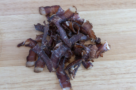 A close up view of a pile of south african biltong on a wood cutting board Imagens