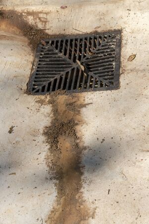A close up view of dirt and sand that has dried leading to a metal grib leading to the drains Imagens