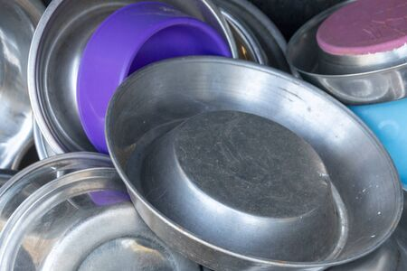 A close up view of metal and plastic dogs bowls all in a pile