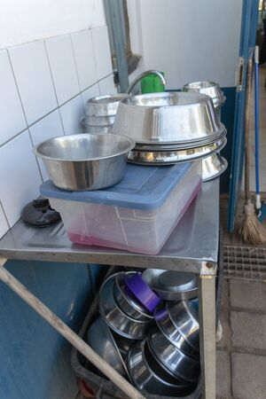 A close up view of metal dogs dishes piled up on a washing sink waiting to be cleaned
