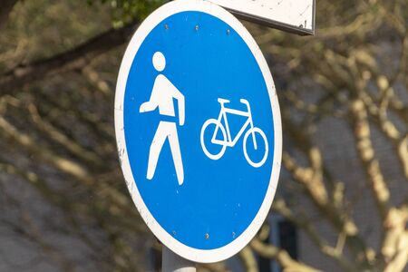 A close up view of a road sign for people and bicycles lane only