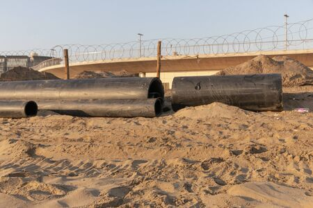 A close up view of large black rubber pipes waiting to be layed into the sand Imagens