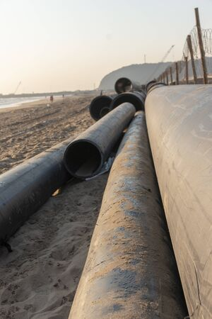 A close up view of large black rubber pipes waiting tobe layed into the sand Imagens
