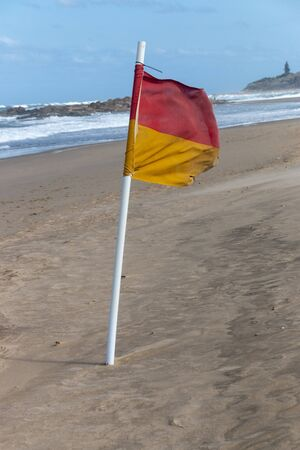 A close up view of a flag pole on the beach to show the designated swimmimg areas on a very windy day Imagens