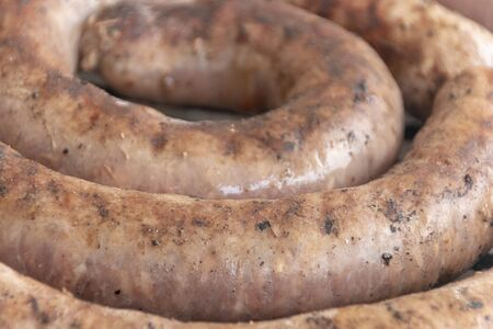 A close up view of beef sausage or boerawors cooking on a open braai or barbecue on a warm summers day  Stock Photo
