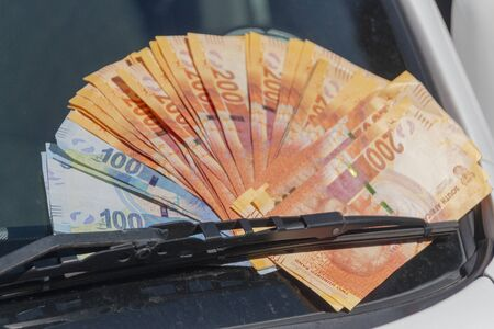 A close up view of one and two hundred rand notes under a sindscreen wiper to show the cost of car parts ans cars Stock Photo