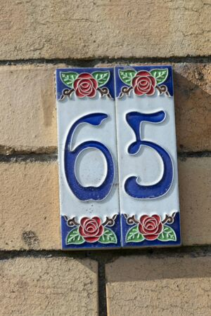 a close up view of the number sixty five embosed on a clay plate for outside your front door