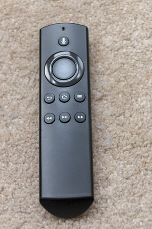 a close up view of a black smart tv remote placed on the carpet