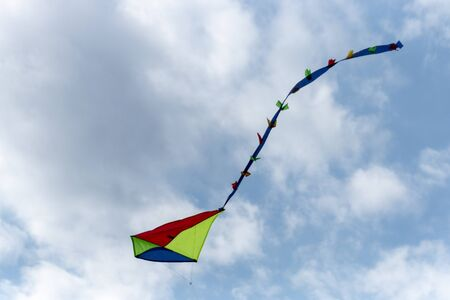 a close up view of a bright coloured kite flying high up in the air