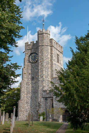 Kent-August-2020-England- a view of the side of a old stone church with a large balck and gold clock on the side