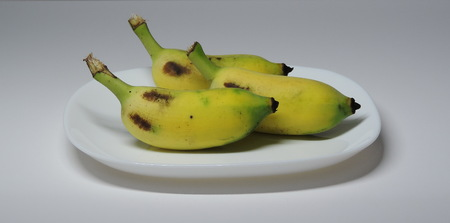 3 cultivated banana on a white plate.