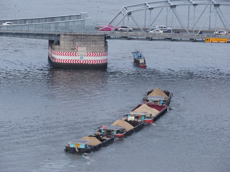 Tug boat that carrying sand was passing under the bridge. 版權商用圖片