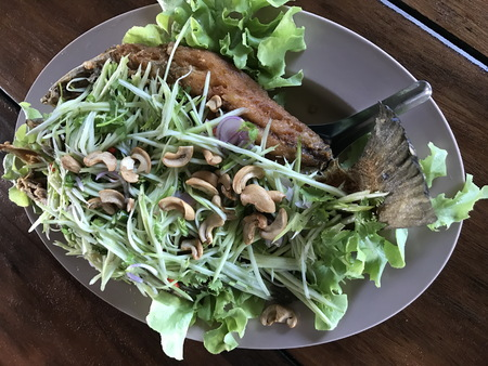 Deep Fried Sea Bass with Spicy Green Mango Salad. Stock Photo