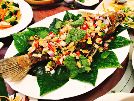 Fried snapper served with mixed herbal and special sauce in Thailand. 免版税图像