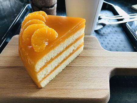 A piece of orange cake served on wooden butcher.