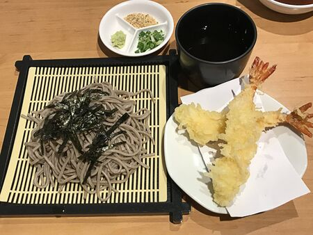 Tenzaru soba or Japanese cold buckwheat noodles served with tempura shrimp.
