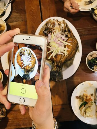 Take pictures of Thai style Deep Fried Sea Bass served with Green Mango Salad with mobile phone.