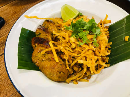 Northern style curry crispy noodle served with Sai ua or Northern Thai sausage or Chiang Mai sausage in Thailand.