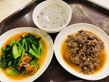 Brown rice porridge served with 'Stir fried crispy pork with kale' and 'Stir fried minced pork with salted Chinese black olive' in Thailand.