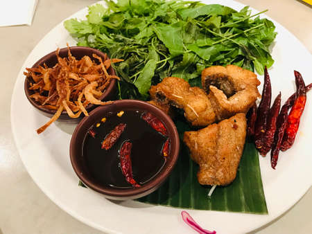 Deep fried catfish served with neem and sweet fish sauce in Thailand. Фото со стока