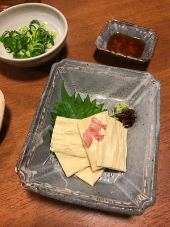 Fresh tofu skin served with soy sauce and chopped spring onion.