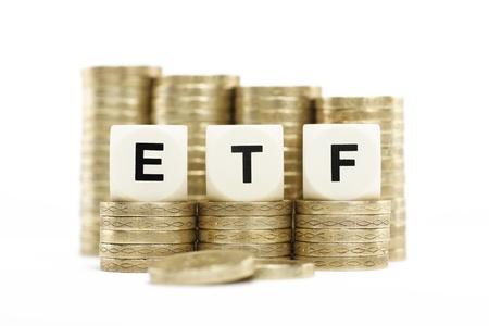 fondos negocios: ETF Exchange Traded Fund en monedas de oro con el fondo blanco Foto de archivo