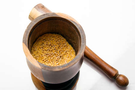 mustard seed: A colorful wood mortar  pestle with mustard seed