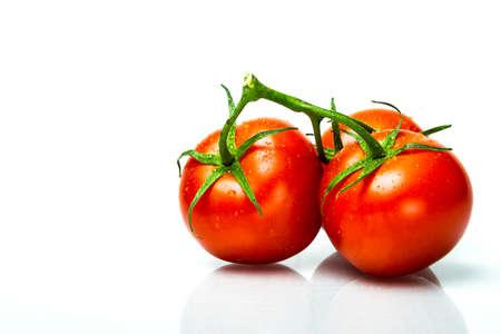 three ripe fresh tomatos on the vine with dew on them Stock Photo