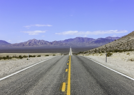 nevada: A long straight road in Death Valley with the desert and mountains in the distance