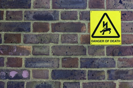 A colorful brick wall with a  Danger of Death sign and pink bubblegum stuck to it