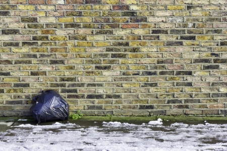 A colorful brick wall with a single black garbage sack left leaning against it