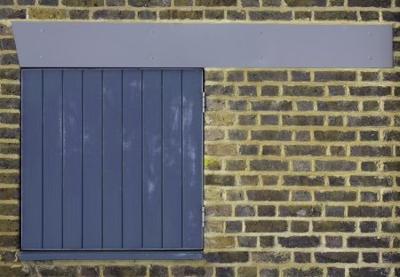 A clean brick wall with a small blue slatted door hatch and pleasing blue grey beam across the top photo